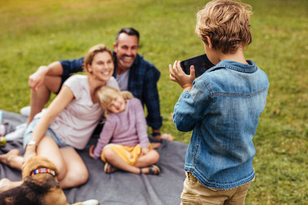 Son photographing family during picnic at park