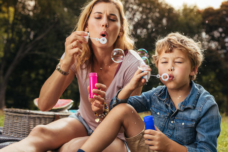 Little boy makes soap bubbles with her mom in the park