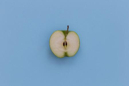 Minimal food green apple half healthy fruit blue background