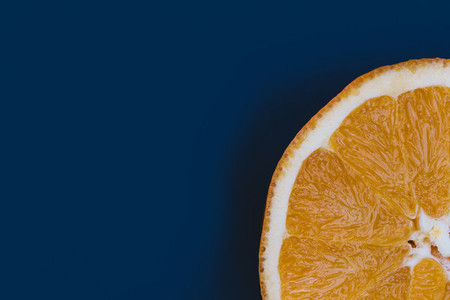 Minimal food orange fruit slice blue background