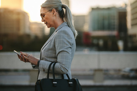 Businesswoman texting on phone while walking outdoor