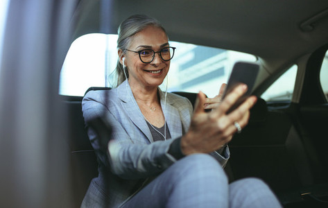Business woman in car making a video call with smartphone