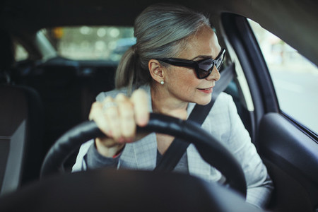Beautiful businesswoman looking away while driving car