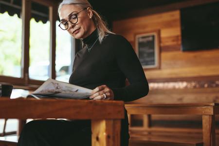 Senior woman reading a magazine at cafe