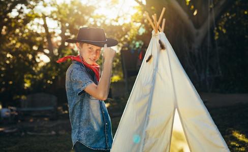 Little boy posing in cowboy hat in backyard