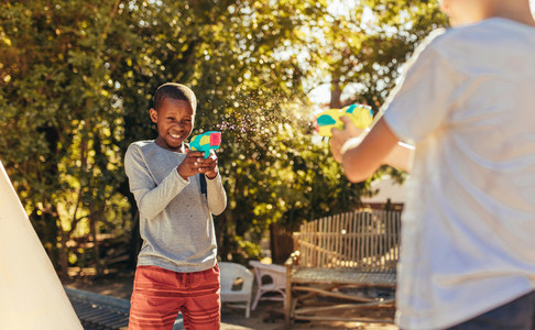 Children enjoys playing with squirt guns outdoors
