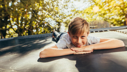 Little boy resting on trampoline after playing