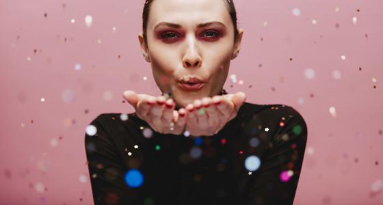 Beautiful female model blowing glitters
