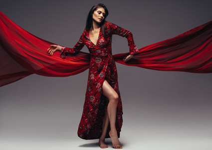 Fashion woman in fluttering red long dress