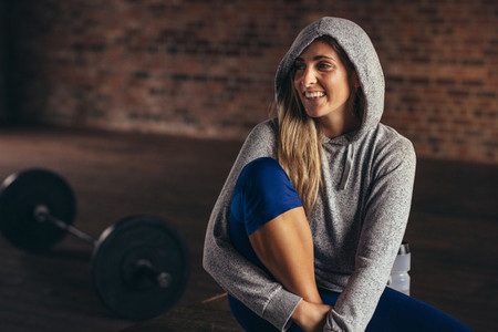 Smiling woman in hoodie relaxing at fitness studio