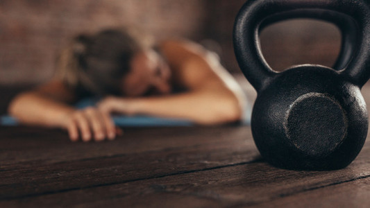 Cross training gym with woman resting after workout