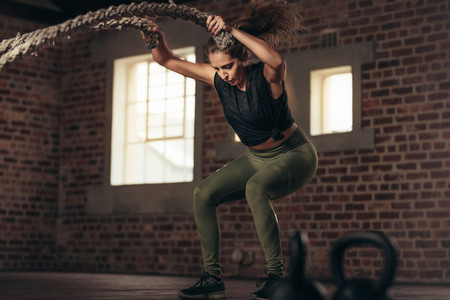 Fitness woman using training ropes for exercise at gym