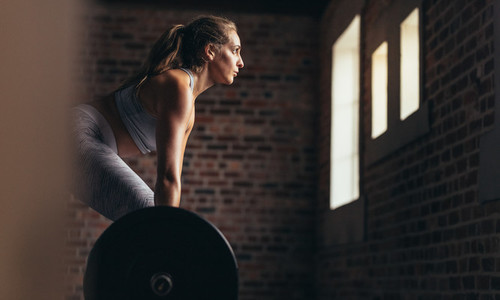 Athlete doing weight lifting exercise in gym