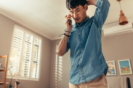 Man looking stressed while answering phone call