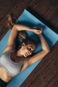 Woman relaxing on yoga mat after workout