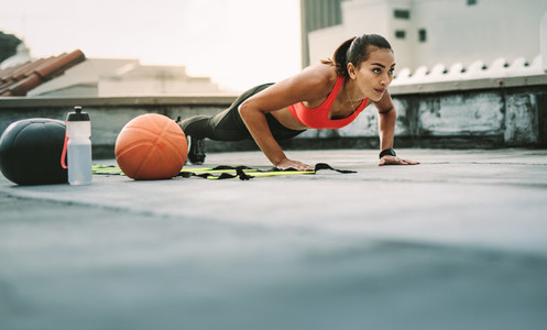 Female athlete doing fitness workout on rooftop