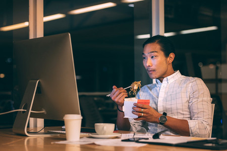 Asian businessman having dinner while working late in office
