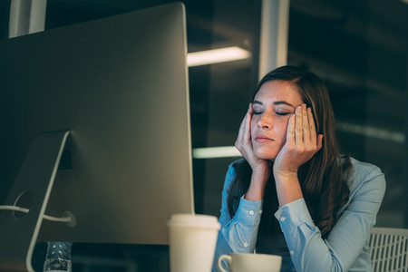 Woman entrepreneur sitting in office looking tired