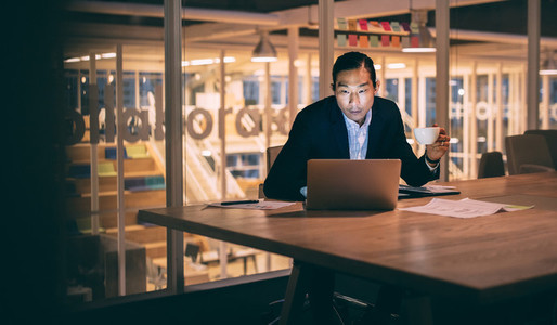 Businessman sitting late night in office working on laptop