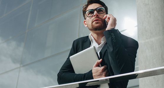 Business person holding a laptop talking on cell phone