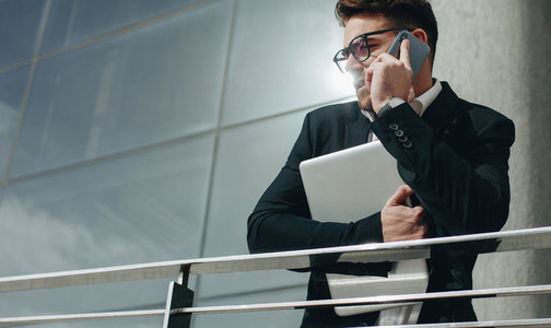 Businessman talking on mobile phone holding a laptop