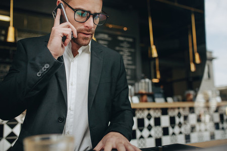 Businessman at a restaurant talking over mobile phone