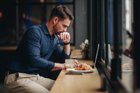 Businessman working on laptop sitting in a restaurant