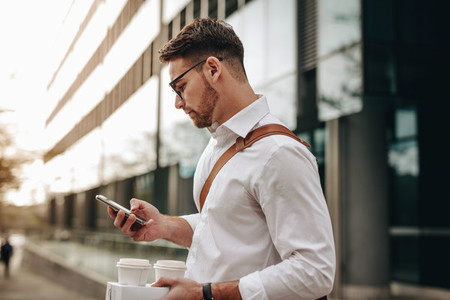 Businessman checking mobile phone standing on street