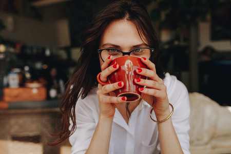 Woman with glasses having a cup of coffee