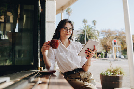 Businesswoman at cafe with cup of coffee and digital tablet