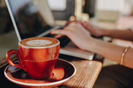 Cup of coffee on table with woman using laptop