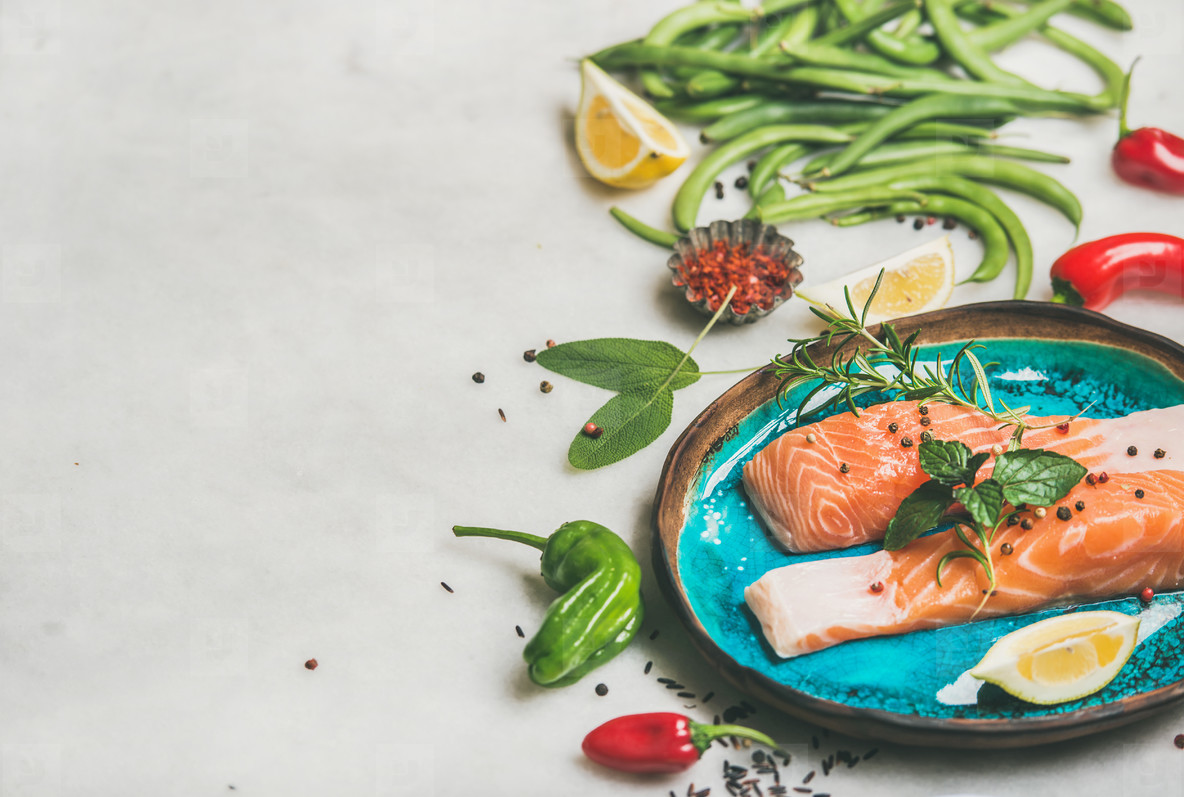 Raw salmon steaks with vegetables  greens  rice in blue plate