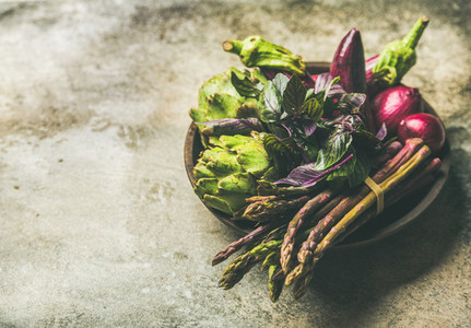 Flat lay of green and purple vegetables on plate  concrete background