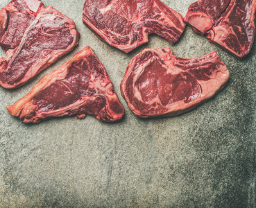 Porterhouse  t bone and rib eye steaks over grey background