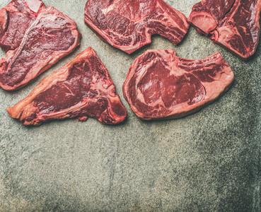 Porterhouse t bone and rib eye steaks over grey background