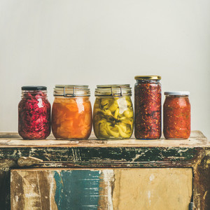 Autumn pickled vegetables in jars placed in line square crop