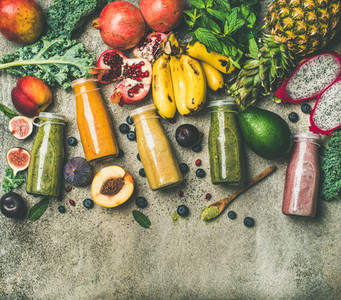 Colorful smoothies in bottles with fresh tropical fruit copy space