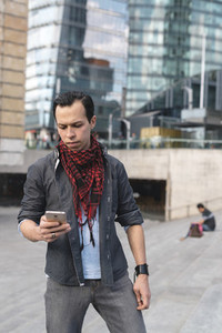 Stylish young man using phone outdoors
