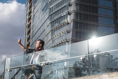 Trendy man taking selfie on urban background
