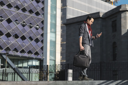 Contemporary man with phone and bag on street