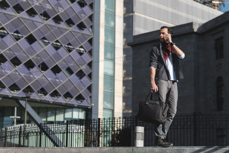 Casual ethnic man with bag speaking on phone
