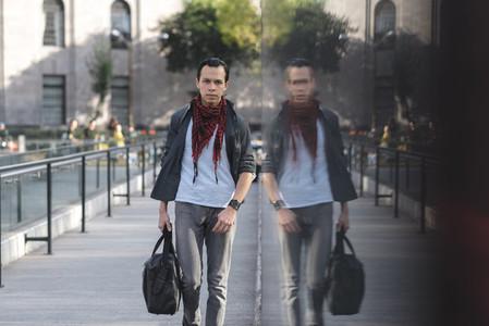 Modern Latino man with bag walking on street
