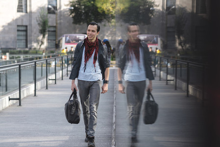 Modern Latino man with bag walking on street