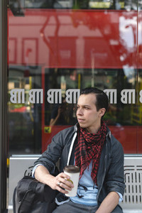Stylish ethnic man having coffee on bench