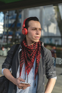 Stylish ethnic man in headphones outdoors
