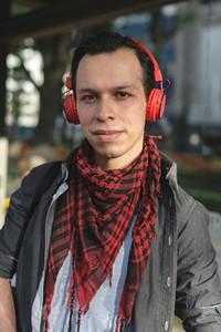 Stylish ethnic man in headphones outdoors