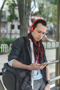 Man with phone and headphones on street