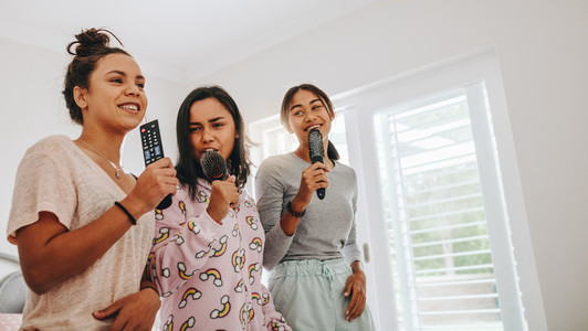 Girls having fun singing songs at a sleepover