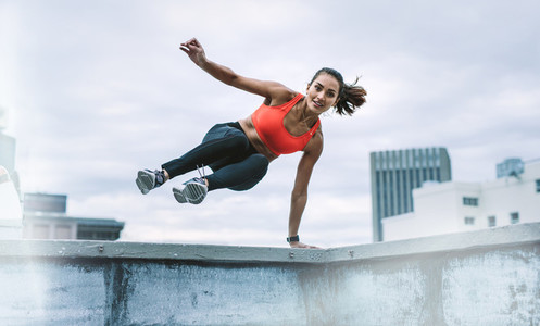 Woman athlete jumping onto the rooftop from the fence