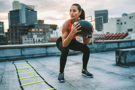 Female athlete doing squats holding a medicine ball